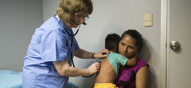 Child with mother receiving care from a volunteer doctor